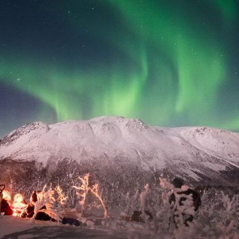 Bonfire under northern lights in Arctic Circle in Norway